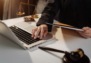 Justice and law concept. Female judge in a courtroom with the gavel working with digital tablet computer docking keyboard on wood table.