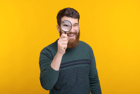 man looking through magnifying glass while standing over yellow background