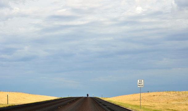 A lone biker rides their motorcycle on an empty highway through yellow fields towards a summer storm - South Dakota, USA