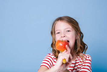 beautiful young girl is posing with red apple in front of blue background