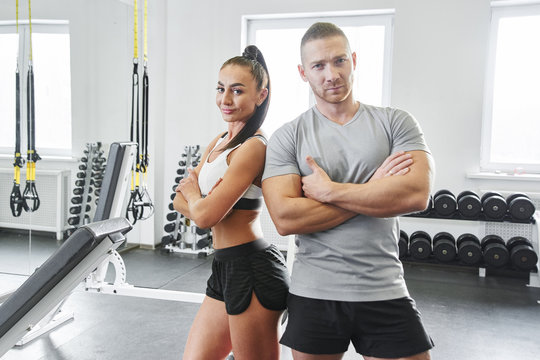 Muscular handsome man and sexy brunette woman with fitness bodies posing in gym, concept of sports nutrition and training program
