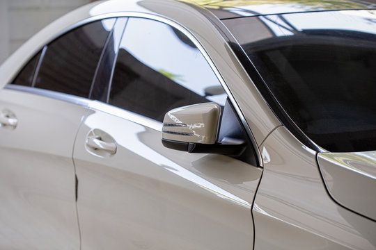 Rear-view mirror or door mirror closed for safety at car park, Side mirror of gray car , black tinted glass