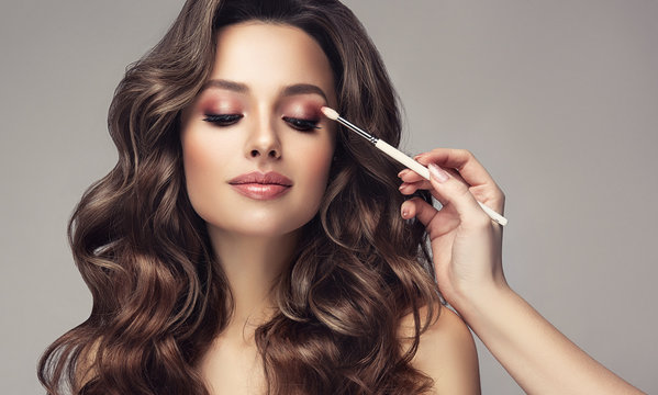 Makeup artist applies  eye shadow  . Beautiful woman with make-up face. Hand of visagiste, painting  cosmetics of young beauty  model girl . Make up in process