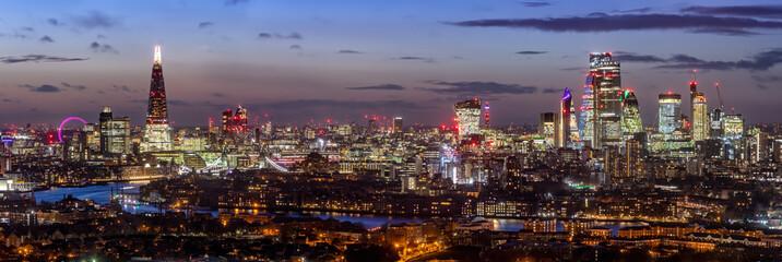 Fotomurales - Panorama der modrnen Skyline von London, Großbritannien, am Abend mit den beleuchteten Hochhäusern an der Themse und zahlreichen Sehenswürdigkeiten