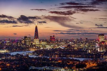 Fotomurales - Die markante Skyline von London am Abend mit den beleuchteten Hochhäusern entlang der Themse und zahlreichen Sehenswürdigkeiten, Großbritannien