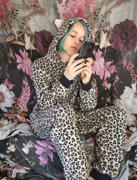 Teenager wearing leopard onesie jumpsuit with blue hair holding mobile phone in her hands