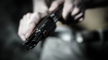 Man chambering a round in a .45 pistol. Close up with shallow depth of field.