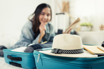 focus vintage hat on green suitcase with young asian woman traveler prepare and packing clothes into suitcase for holiday vacation at home, summer holiday, backpacker, travel and lifestyle concept