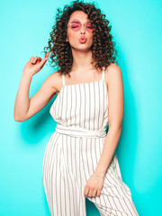 Portrait of beautiful smiling model with afro curls hairstyle dressed in summer hipster...