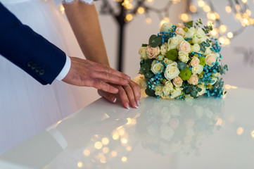 picture of man and woman holding hands over wedding flowers background. Marriage concept.