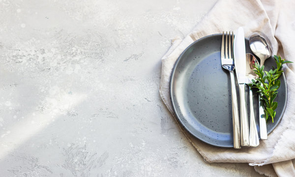 Elegant table setting with black ceramic plate, cutlery and canvas napkin on grey stone background. Space for text.