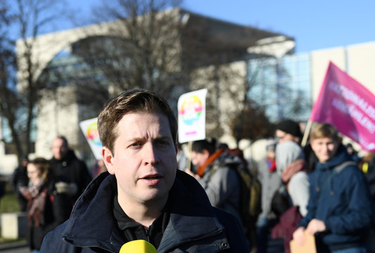 Social Democratic Party deputy leader Kevin Kuehnert speaks to a TV journalist during a demonstration organized by an alliance of youth organizations in front of the Chancellery in Berlin