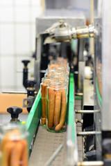 Gläser mit Würstchen auf dem Fliessband in der Produktion im Lebensmittelwerk