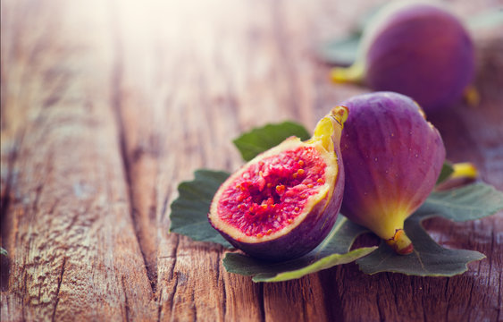 Ripe fig fruits with leaf close-up. Beautiful sweet fresh organic figs on a wooden table. Border label design. Healthy vegan food
