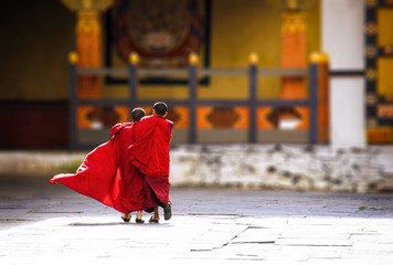 Konigreich Bhutan, Asien, Himalaya. Zwei junge Novizen in Innenhof eines Kloster laufen umarmt zum Tempel. Ihre roten Gewänder leuchten in der Sonne und wehen im Wind.