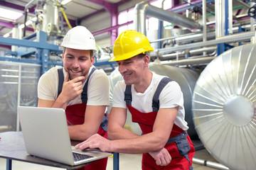 Mechanics repair a machine in a modern industrial plant - profession and teamwork
