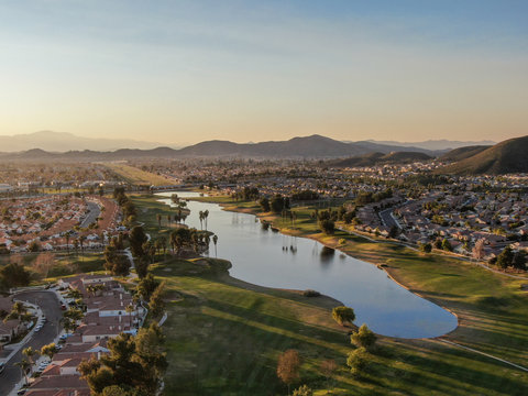 Aerial view of golf course surrounded by town houses and luxury villas during sunset time. Temecula, California, USA