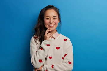 Pretty Asian woman has toothy smile, rouge cheeks, wears jumper with heart print, expresses sincere emotions, has dark hair combed in pony tail, isolated over blue background. Happiness concept
