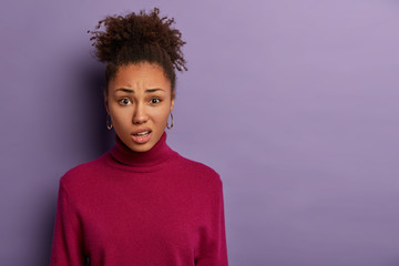 Human facial expressions concept. Displeased Afro woman smirks face and purses lips, reacts on hearing something unpleasant, wears casual jumper, models over purple wall with blank space aside