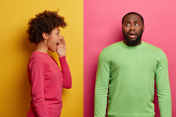 Emotive young curly woman stands in profile and screams loudly at guilty man who has embarrassed face expression, made big mistake, wear bright jumpers, isolated on pink and yellow stuio wall