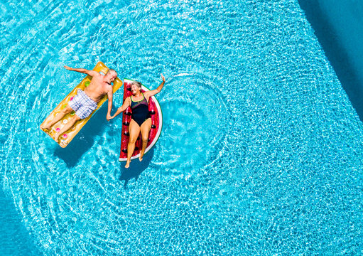 Vertical view of happy couple of old senior people enjoying the summer holiday vacation at the blue water pool with coloured treny lilos together with fun and love