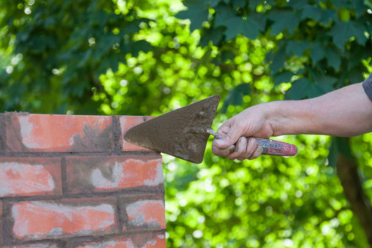 Masonry works, male hand working with a trowel, repairing a chimney from red bricks on a roof of country house