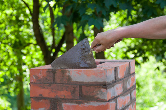 Masonry works,  male hand working with a trowel, repairing a chimney from red bricks on a roof