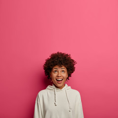 Happy ethnic girl concentrated above on ceiling, sees amazing thing upwards, smiles joyfully, has funny curious look up, wears casual clothes, isolated over rosy wall with copy space. Wow, interesting