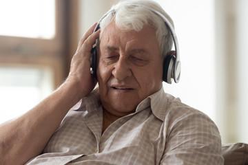 Modern elderly man enjoy listening to music in headphones