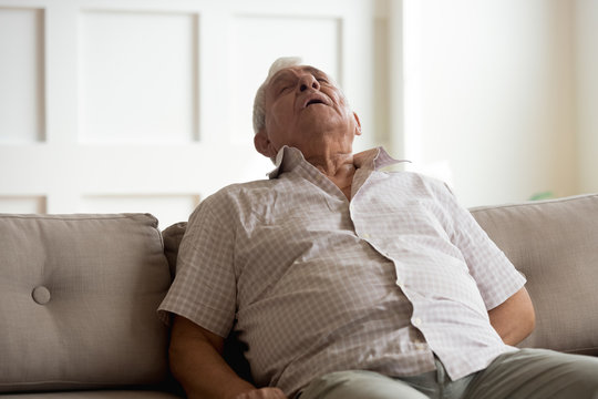 Exhausted elderly man fall asleep on couch at home