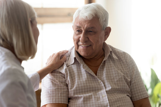 Supportive female nurse take care of senior male patient