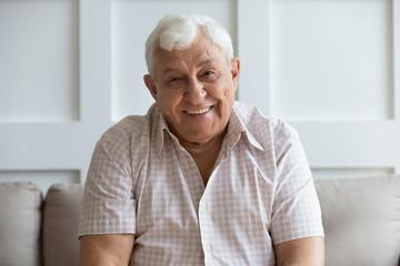 Headshot portrait of smiling mature man relaxing on sofa