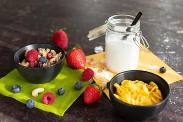 leckeres Müsli mit frischen Beeren und Cornflakes in Schüsselchen. Dazu Kokosmilch im Einmachglas mit Strohhalm