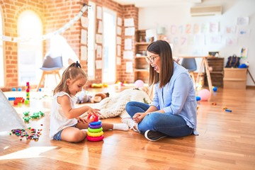 Caucasian girl kid playing and learning at playschool with female teacher. Mother and daughter at playroom playing with inteligence toys