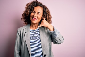Wall Mural - Middle age beautiful businesswoman wearing elegant jacket over isolated pink background smiling doing phone gesture with hand and fingers like talking on the telephone. Communicating concepts.