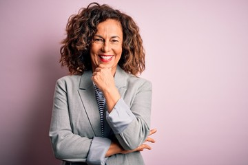 Wall Mural - Middle age beautiful businesswoman wearing elegant jacket over isolated pink background looking confident at the camera smiling with crossed arms and hand raised on chin. Thinking positive.