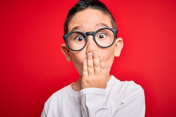 Young little smart boy kid wearing nerd glasses over red isolated background cover mouth with hand shocked with shame for mistake, expression of fear, scared in silence, secret concept Fototapete