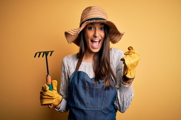 Young beautiful farmer woman wearing apron and hat using rake over yellow background screaming proud and celebrating victory and success very excited, cheering emotion