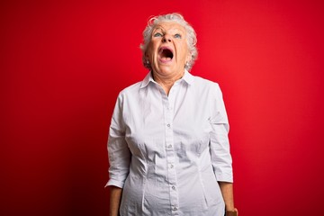 Senior beautiful woman wearing elegant shirt standing over isolated red background angry and mad...