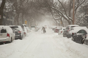 Fototapeta Man w alking in a street with car covered of snow in a street in Canada