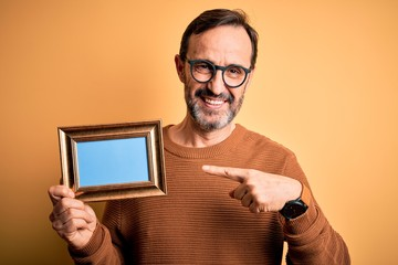 Middle age hoary man wearing glasses holding vintage frame over isolated yellow background very happy pointing with hand and finger