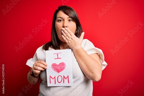 Beautiful brunette plus size woman holding love mom message celebrating mothers day cover mouth with hand shocked with shame for mistake, expression of fear, scared in silence, secret concept