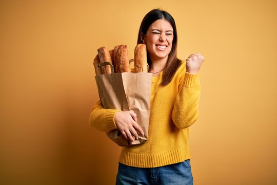 Young beautiful woman holding a bag of fresh healthy bread over yellow background very happy and excited doing winner gesture with arms raised, smiling and screaming for success. Celebration concept.