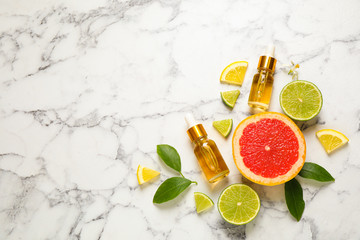 Flat lay composition with bottles of citrus essential oil on white marble background. Space for text