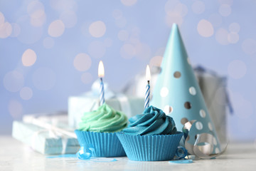 Delicious birthday cupcakes with cream and burning candles on white table