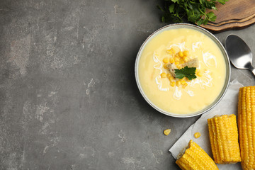Delicious corn cream soup served on grey table, flat lay. Space for text