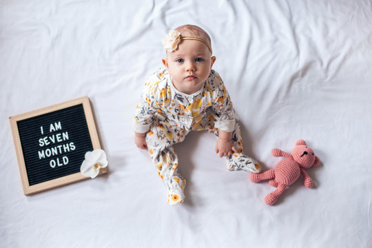 7 Seven months old baby girl sitting on white background with letter board and teddy bear. Flat lay composition.