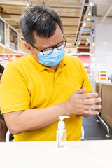 Asian man with face mask apply disinfectant sanitizer onto hand before meal