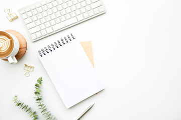 Wall Mural - Blank notebook is on top of white minimal office desk table with cup of latte coffee and supplies. Top view with copy space, flat lay.