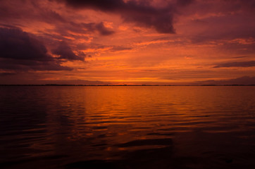 In de dag Rood traf. Sunset over Lake Chascomus, orange beautiful sky reflected in the water surface